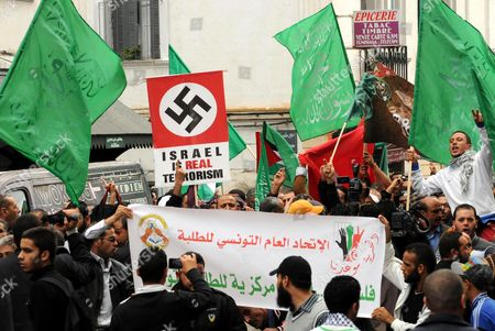 Tunisian Protesters Hold Anti Israeli Placards and Green Islamists Flags During a Demonstration Against the Israeli's Attacks in Gaza Strip in Tunis Tunisia 16 November 2012 Several Hundred People Demonstrated in Tunisia on 16 November in Support of the People of Gaza As an Israeli Military Offensive Aimed at Ongoing Rocket Fire From Gaza Entered Its Third Day on 17 November a Delegation Led by Foreign Minister Rafik Abdessalem Will Pay a Visit to Gaza a Day After a Visit by Egyptian Prime Minister Hesham Qandil Tunisia Tunis