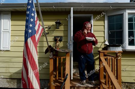 Alan Anderson Stands on His Porch Eating Soup For Breakfast While Taking a Break From Gutting His Home As People Continue to Try and Recover From the Aftermath of Hurricane Sandy in the New Dorp Neighborhood of Staten Island New York Usa 15 November 2012 Many Communities in the Area Are Still Working on Clean Up From the Flooding Caused by the Storm Surge and Are Without Power United States Staten Island