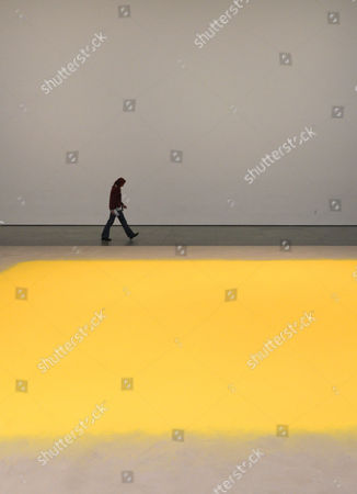 A Woman Walks Past the Site Specific Installation 'Pollen For Hazelnut' by Artist Wolfgang Laib of Germany at the Museum of Modern Artâ in New York New York Usa 01 March 2013 the Work is Made Up Entirely of Hazelnut Pollen and and is on View Until 11 March 2013 United States New York