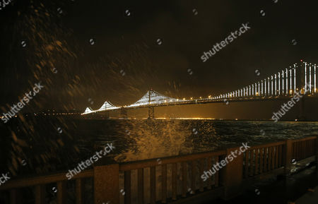 The San Francisco Bay Bridge is Lit Up During the Official Bay Lights Grand Lighting As Waves Crash Against the Sea Wall in San Francisco California Usa 05 March 2013 the Bay Lights is the World's Largest Led Light Sculpture It Stretches 1 8 Miles (2 89km) Wide and is 500 Feet (152 4m) High the Light Exhibit Has 25 000 White Led Lights That Are Individually Programmed by Artist Leo Villareal to Create a Never-repeating Display Across the Bay Bridge's West Span Through 2015 United States San Francisco