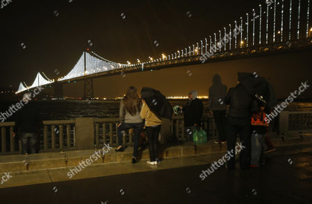 A Group of People Brave the Rain to Look at the Newly Lit Up San Francisco Bay Bridge After the Official Bay Lights Grand Lighting in San Francisco California Usa 05 March 2013 the Bay Lights is the World's Largest Led Light Sculpture It Stretches 1 8 Miles (2 89km) Wide and is 500 Feet (152 4m) High the Light Exhibit Has 25 000 White Led Lights That Are Individually Programmed by Artist Leo Villareal to Create a Never-repeating Display Across the Bay Bridge's West Span Through 2015 United States San Francisco
