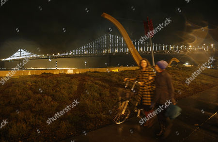 People Walk Past the Newly Lit Up San Francisco Bay Bridge and the Cupids Span Sculpture After the Official Bay Lights Grand Lighting in San Francisco California Usa 05 March 2013 the Bay Lights is the World's Largest Led Light Sculpture It Stretches 1 8 Miles (2 89km) Wide and is 500 Feet (152 4m) High the Light Exhibit Has 25 000 White Led Lights That Are Individually Programmed by Artist Leo Villareal to Create a Never-repeating Display Across the Bay Bridge's West Span Through 2015 United States San Francisco