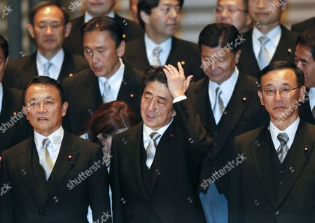 Newly Appointed Japanese Prime Minister Shinzo Abe (c) Combs His Hair During a Photo Session at the Imperial Palace with Former Prime Minister and Newly Appointed Finance Minister Taro Aso (l) New Justice Minister Sadakazu Tanigaki (r) and Other Cabinet Ministers After Being Attested by Emperor Akihito in Tokyo Japan 26 December 2012 Japan Tokyo