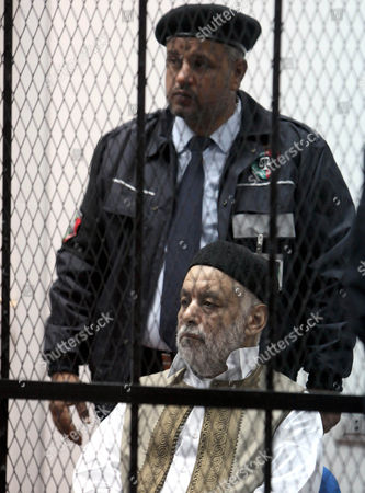 Former Libyan Prime Minister Baghdadi Al-mahmoudi Looks on As He Sits Behind Bars Next to a Security Agent in a Cage During the Second Hearing of His Trial at a Courthouse in Tripoli Libya 10 December 2012 Al-mahmoudi Faces Charges of Involvement in Crimes Under the Gaddafi Rule Which was Toppled Last Year He Served As Prime Minister From 2006 Until August 2011 when He Fled to Tunisia After Insurgents Seized Control of Tripoli Virtually Ending Gaddafis 42-year Rule Tunisia Extradited Al-mahmoudi to Libya in June 2012 Libyan Arab Jamahiriya Tripoli