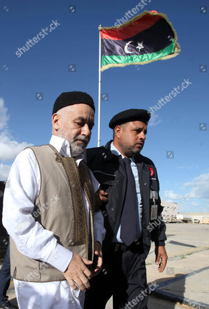 Former Libyan Prime Minister Baghdadi Al-mahmoudi (l) Arrives For the the Second Hearing of His Trial at a Courthouse in Tripoli Libya 10 December 2012 Al-mahmoudi Faces Charges of Involvement in Crimes Under the Gaddafi Rule Which was Toppled Last Year He Served As Prime Minister From 2006 Until August 2011 when He Fled to Tunisia After Insurgents Seized Control of Tripoli Virtually Ending Gaddafis 42-year Rule Tunisia Extradited Al-mahmoudi to Libya in June 2012 Libyan Arab Jamahiriya Tripoli