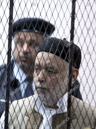 Former Libyan Prime Minister Baghdadi Al-mahmoudi Looks on As He Sits Behind Bars in a Cage During the Second Hearing of His Trial at a Courthouse in Tripoli Libya 10 December 2012 Al-mahmoudi Faces Charges of Involvement in Crimes Under the Gaddafi Rule Which was Toppled Last Year He Served As Prime Minister From 2006 Until August 2011 when He Fled to Tunisia After Insurgents Seized Control of Tripoli Virtually Ending Gaddafis 42-year Rule Tunisia Extradited Al-mahmoudi to Libya in June 2012 Libyan Arab Jamahiriya Tripoli