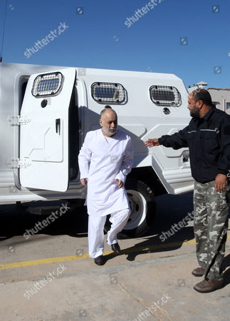 Former Libyan Prime Minister Baghdadi Al-mahmoudi (l) Arrives For the Fourth Hearing Session of His Trial at a Courthouse in Tripoli Libya 11 February 2013 Al-mahmoudi Faces Charges of Involvement in Crimes Under the Gaddafi Rule Which was Toppled in 2011 He Served As Prime Minister From 2006 Until August 2011 when He Fled to Tunisia After Insurgents Seized Control of Tripoli Virtually Ending Gaddafis 42-year Rule Tunisia Extradited Al-mahmoudi to Libya in June 2012 Libyan Arab Jamahiriya Tripoli