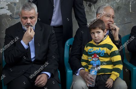 Stock Photo of Malaysian Prime Minister Najib Razak (r) Hugs the Son of Hamas Military Commander Ahmed Al-jaabari who was Killed in an Israeli Air Strike As He Sits Next to Senior Hamas Leader Ismail Haniyeh (r) During His Visit to Al-jaabari Family in Gaza Strip 22 January 2013 - Gaza Strip