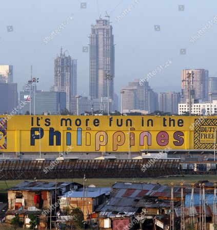 High Rise Buildings Loom Over Shanties in Paranaque City South of Manila Philippines 05 February 2013 American Economist Nouriel Roubini Branded the Philippines and Indonesia As the the New Tigers of Asia As They Defied Global Economic Trends Recording Impressive Growth Rates Hitting Historic Highs in Their Stock Markets and Attracting Foreign Direct Investments the Philippine Economy Grew at a Faster-than-expected Rate of 6 6 Per Cent in 2012 Making It One of the Best Performing Economies in Asia the Gross Domestic Product (gdp) Growth was Better Than Economists' Projections and the Government's Target of 5 Per Cent to 6 3 Per Cent Philippines Manila