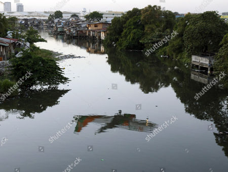 An Airplane is Reflected in the Waters of a Pond As It Flies Over Shanties Erected on the Banks of a Murky River in Paranaque City South of Manila Philippines 05 February 2013 American Economist Nouriel Roubini Branded the Philippines and Indonesia As the the New Tigers of Asia As They Defied Global Economic Trends Recording Impressive Growth Rates Hitting Historic Highs in Their Stock Markets and Attracting Foreign Direct Investments the Philippine Economy Grew at a Faster-than-expected Rate of 6 6 Per Cent in 2012 Making It One of the Best Performing Economies in Asia the Gross Domestic Product (gdp) Growth was Better Than Economists' Projections and the Government's Target of 5 Per Cent to 6 3 Per Cent Philippines Manila