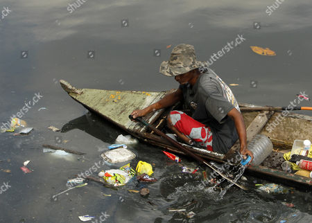 A Man Collects Recyclable Materials at a River in Manila Philippines 06 February 2013 American Economist Nouriel Roubini Branded the Philippines and Indonesia As the the New Tigers of Asia As They Defied Global Economic Trends Recording Impressive Growth Rates Hitting Historic Highs in Their Stock Markets and Attracting Foreign Direct Investments the Philippine Economy Grew at a Faster-than-expected Rate of 6 6 Per Cent in 2012 Making It One of the Best Performing Economies in Asia the Gross Domestic Product (gdp) Growth was Better Than Economists' Projections and the Government's Target of 5 Per Cent to 6 3 Per Cent Philippines Manila