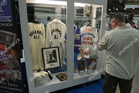 A Man Stops to Look at a Display Case Showing Two of Muhammad Ali's White Robes Including His 5th Street Gym Training-worn Robe (2-l) and an Outfit (r) of George Foreman on Display at the National Sports Collectors Convention in Baltimore Maryland Usa 01 August 2012 a Collection of Boxing Memorabilia of Hall of Fame Trainer Angelo Dundee Will Be Available in an Online Auction by Scp Auctions November 2012 Renowned Trainer Angelo Dundee was a Guiding Force to the Two Most Celebrated Fighters of His Era Muhammad Ali and Sugar Ray Leonard and Fifteen Other World Champions United States Baltimore