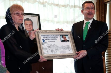 Marina Karlova, Melih Gokcek Ankara Mayor Melih Gokcek presents a framed copy of his municipality's decision to rename the street that houses the Russian Embassy after the ambassador who was killed, to Marina Karlova, the widow of Russia's ambassador to Turkey Andrei Karlov, in Ankara, Turkey, . Municipality workers then replaced the street sign with one inscribed with Karlov's name. Karlov was shot dead Dec. 19 while delivering a speech at the opening of a photo exhibition
