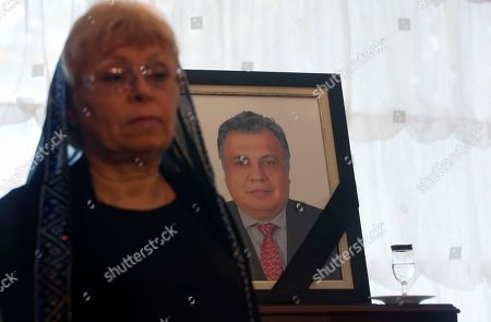 Marina Karlova, the widow of Russia's ambassador to Turkey Andrei Karlov, stands next to his photograph during a ceremony at the Russian embassy, after Ankara Mayor Melih Gokcek presented her with a copy of his municipality's decision to rename the street that houses the Russian Embassy after Karlov in Ankara, Turkey, . Municipality workers then replaced the street sign with one inscribed with Karlov's name. Karlov was shot dead Dec. 19 while delivering a speech at the opening of a photo exhibition