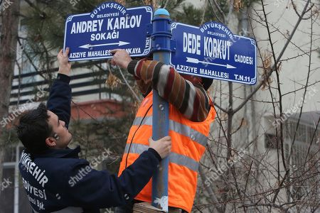 Ankara municipal workers replace the street sign with one inscribed with the name of Andrei Karlov, Russia's ambassador to Turkey, in Ankara, Turkey, . Karlov was shot dead Dec. 19 while delivering a speech at the opening of a photo exhibition in Ankara