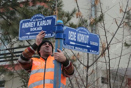 An Ankara municipal worker replaces the street sign with one inscribed with the name of Andrei Karlov, Russia's ambassador to Turkey, in Ankara, Turkey, . Karlov was shot dead Dec. 19 while delivering a speech at the opening of a photo exhibition in Ankara