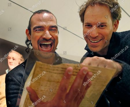 """Javier Munoz, David Korins Javier Munoz, left, who plays Alexander Hamilton in the enormously popular Broadway hip-hop musical """"Hamilton,"""" laughs with the show's set designer David Korins as they read a letter from Hamilton to an unnamed recipient, possibly Jeremiah Wadsworth, about the 1796 presidential election, at Sotheby's auction house in New York. This and a trove of artifacts related to Alexander Hamilton, including love letters to his wife, Eliza, will be offered up for auction at Sotheby's Jan. 18, part of """"Americana week."""" Munoz says holding and reading Hamilton's private thoughts about everything from his love life to war in America will have a deep effect on his Broadway performance"""
