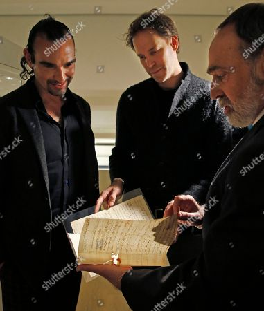 """Javier Munoz, David Korins, Selby Kiffer Javier Munoz, left, who plays Alexander Hamilton in the Broadway megahit """"Hamilton,"""" the musical's set designer David Korins, center, and Sotheby's expert on books and manuscripts Selby Kiffer, look at a document written by or related to Hamilton, in New York. A trove of historic American artifacts pertaining to Hamilton that belong to Hamilton's descendants will be put on the auction block on Jan. 18"""