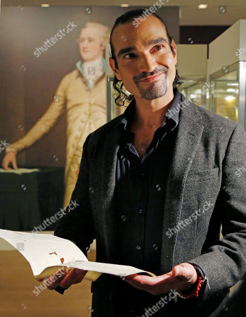 """Javier Munoz, who plays Alexander Hamilton in the hit Broadway musical, reacts as he reads a letter from Hamilton's son Patrick to his father that starts with the words """"Dear Papa,"""", in New York. The letter is among a trove of artifacts related to Alexander Hamilton, including love letters to his wife Eliza, that will be offered up for auction at Sotheby's Jan. 18. Hamilton set designer David Korins, who also helped Sotheby's on the Americana auction's space, of which the letters are a part, jokingly warned the Broadway star not to let his tears fall on Hamilton's delicate old letter paper"""