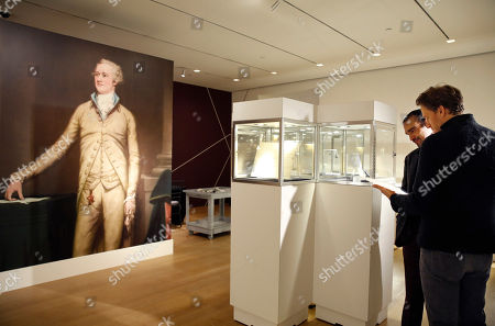"""Javier Munoz, David Korins A portrait of Alexander Hamilton decorates an entire wall, left, as Javier Munoz, who plays Alexander Hamilton in the Broadway megahit musical """"Hamilton,"""" and the musical's set designer David Korins, right, pore over documents written by or related to Hamilton, at Sotheby's auction house in New York. The artifacts, belonging to Hamilton's descendants, will be put on the auction block at Sotheby's Jan. 18"""