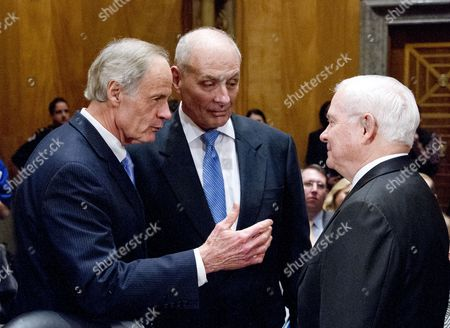General John F. Kelly, USMC (Retired), center, speaks with United States Senator Tom Carper (Democrat of Delaware), left, and former US Secretary of Defense Robert Gates, right, as he arrives to testify before the United States Senate Committee on Homeland Security and Governmental Affairs confirmation hearing on his nomination to be Secretary, US Department of Homeland Security on Capitol Hill in Washington, DC.