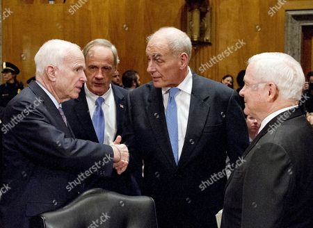 General John F. Kelly, USMC (Retired), right center, shakes hands with United States Senator John McCain ((Republican of Arizona), left, as US Senator Tom Carper (Democrat of Delaware), center left, and former US Secretary of Defense Robert Gates, right, look on as he arrives to testify before the United States Senate Committee on Homeland Security and Governmental Affairs confirmation hearing on his nomination to be Secretary, US Department of Homeland Security on Capitol Hill in Washington, DC.
