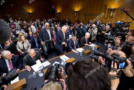 Secretary of State-designate Rex Tillerson, center, accompanied by, from left, former Defense Secretary Robert Gates, former Georgia Sen. San Nunn, Sen. Ted Cruz, R-Texas, and Senate Majority Whip John Cornyn of Texas, takes his seat on Capitol Hill in Washington, prior to testifying at his confirmation hearing before the Senate Foreign Relations Committee