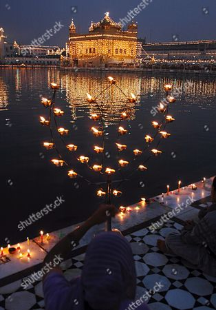 Devotees Light Candles and Decorated Lamps Around the Holy Pond of the Golden Temple As the Mark of Celebration On the Occasion of the Birth Anniversary of the First Guru of the Sikhs Guru Nanak Dev Ji in Amritsar City Punjab India On Sunday 05 November 2006
