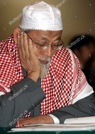 Indonesian Muslim Cleric Abu Bakar Ba'asyir Read a Printout As He Listens to a Witness During His Trial at the Court Room in Jakarta Indonesia Thursday 16 December 2004 Ba'asyir Accused of Leading an Al Qaeda-linked Militant Network and of Planning Or Inciting the Group to Carry out Attacks in the World's Most Populous Muslim Nation