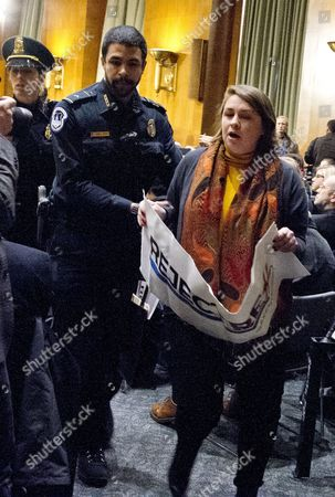A protestor is led out of the United States Senate Committee on Foreign Relations hearing considering the nomination of Rex Wayne Tillerson, former chairman and chief executive officer of ExxonMobil to be Secretary of State of the US