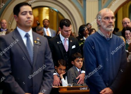 State Representative Chris Hansen, D-District 6, center, bows his head during an invocation, holding his sons Ashwin, 8, left, and Sachin, 9, during the opening session of the 2017 Colorado Legislature, at the Capitol, in Denver, . The Colorado Democratic House and Republican Senate are waiting for cues from Washington and from Democratic Gov. John Hickenlooper about the priorities this year