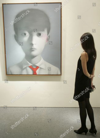 A Christie's Member of Staff Gazes at an Oil On Canvas Painting by Chinese Artist Zhang Xiaogang (born 1958) Entitled 'Boy' Which is Expected to Fetch Over Four Million Hong Kong Dollar (380 500 Euros) at the Forthcoming Christie's Hong Kong Spring Auction From 27-31 May 2007 Hong Kong 24 May 2007