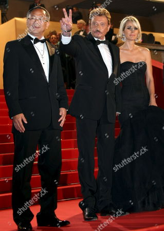 Stock Image of French Rockstar Johnny Hallyday (c) and His Wife Laetitia (r) and Director Johnny to (l) Leave the Gala Screening of Their Film 'Vengeance' by Johnny to Running in Competition During the 62nd Edition of the Cannes Film Festival in Cannes France 17 May 2009