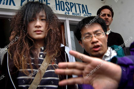 Lio Tsai Lin (l) Daughter of Missing Taiwanese Tourist Huang Su Chin is Escorted by an Unidentified Man After She Identified the Body of Her Mother in the Police Control Room After Her Body Was Fished out From the Dal Lake in Srinagar Kashmir Saturday 08 April 2006 Huang (52) Was Missing Since March 22 Following a Sightseeing Excursion On the Dal Lake