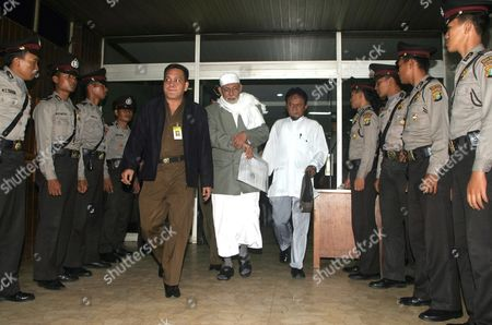 Indonesian Muslim Cleric Abu Bakar Ba'asyir (c) Walks Accompanied by His Student (5-r) and Prosecutor Official (5-l) After He Listens Ali Imron Testemony in His Trial at South Jakarta's Court in Indonesia Thursday 20 January 2005 Ba'asyir is Currently On Trial For Allegedly Planning and Inciting His Followers to Carry out the Bali Bombings in 2002 That Killed Over 200 People Mostly Foreign Holidaymakers and the Attack On American Hotel Chain Jw Marriott in 2003 Which Killed 12 People Mostly Locals Later in the Trial a Former U S State Department Translator Said That 'A U S Presidential Envoy' Asked Megawati to Hand Ov Indonesia Jakarta