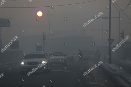 A view of road traffic shrouded in haze in the capital city of Ulaanbaatar, Mongolia, 12 January 2017. Mongolian President Tsakhiagiin Elbegdorj said on 11 January 2017, that air pollution in Ulaanbaatar has reached disaster levels and the city is declared to be in a state of disaster where measures like evacuations are recommended for some areas, according to local media.