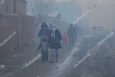 Mongolians wearing masks walk along a road shrouded in haze in the capital city of Ulaanbaatar, Mongolia, 12 January 2017. Mongolian President Tsakhiagiin Elbegdorj said on 11 January 2017, that air pollution in Ulaanbaatar has reached disaster levels and the city is declared to be in a state of disaster where measures like evacuations are recommended for some areas, according to local media.