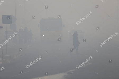 A pedestrian crosses a road shrouded in haze in the capital city of Ulaanbaatar, Mongolia, 12 January 2017. Mongolian President Tsakhiagiin Elbegdorj said on 11 January 2017, that air pollution in Ulaanbaatar has reached disaster levels and the city is declared to be in a state of disaster where measures like evacuations are recommended for some areas, according to local media.