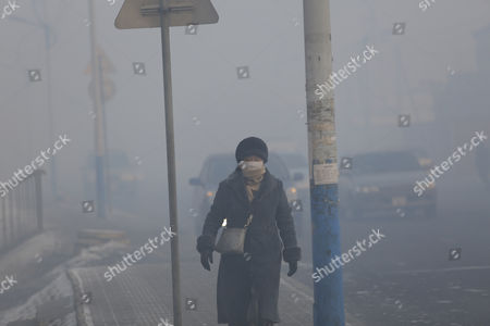 A woman wearing a mask walks along a road shrouded in haze in the capital city of Ulaanbaatar, Mongolia, 12 January 2017. Mongolian President Tsakhiagiin Elbegdorj said on 11 January 2017, that air pollution in Ulaanbaatar has reached disaster levels and the city is declared to be in a state of disaster where measures like evacuations are recommended for some areas, according to local media.