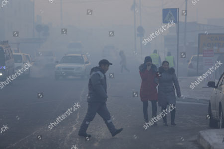 Mongolians walking along a road shrouded in haze in the capital city of Ulaanbaatar, Mongolia, 12 January 2017. Mongolian President Tsakhiagiin Elbegdorj said on 11 January 2017, that air pollution in Ulaanbaatar has reached disaster levels and the city is declared to be in a state of disaster where measures like evacuations are recommended for some areas, according to local media.