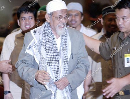 Indonesian Muslim Cleric Abu Bakar Ba'asyir is Escorted by a Court Officer Shortly After Shaking Hands with Militant Activist Witnesses in Jakarta 09 December 2004 Ba'asyir is Accused of Leading an Al Qaeda-linked Militant Network and of Planning Or Inciting the Group to Carry out Attacks in the World's Most Populous Muslim Nation However the Witness Told the Court That Ba'asyir Was not a Member of the Al-qaeda-linked Jamaah Islamiyah (ji) Terrorist Group the Witness Admitted to Being a Top Member of Ji