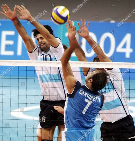 Italian Andrea Sartoretti (7) Spikes the Ball Against Alejandro Spajic (l) and Jorge Alberto Elgueta (r) From Argentina During the Quarter-final Match at the Peace & Friendship Stadium in Athens Wednesday 25 August 2004 Italy Won 3-1 to Advance to the Semi-finals Epa/dpa Vassilis Ververidis