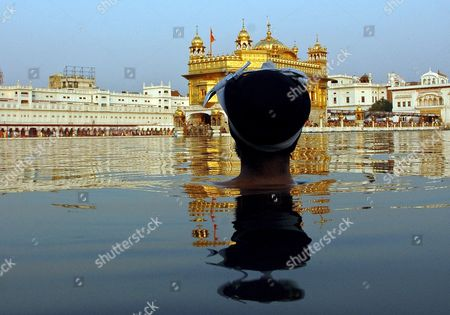 A Sikh Devotee Takes a Holy Dip in the Sacred Pond of the Golden Temple Which is the Most Sacred Place For Sikhs All Over the World On the Occasion of the Birth Anniversary of the Fifth Master Or 'Guru' of the Sikhs Guru Arjan Dev Ji in Amritsar City Punjab India On 02 May 2007 Guru Arjan Dev Ji Compiled and Installed For the First Time the Sri Guru Granth Sahib Ji the Holy Book of Sikh Religion Including Over 2 000 Hymns by Him