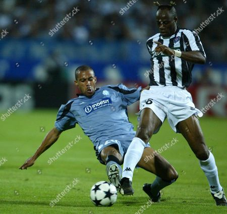 Stock Image of Fk Partizan Belgrade's Taribo West (r) Fights For the Ball with Olympique De Marseille's Steve Marlet During Their Uefa Champions League Soccer Match at Velodrome Stadium at Marseille On Wednesday 01 October 2003