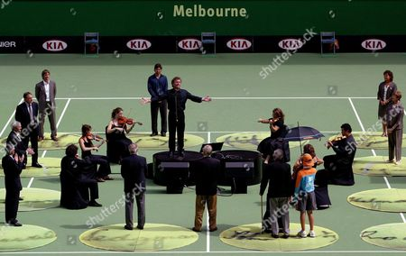 Australian Tenor Peter Brocklehurst Sings As Australia's Greatest Tennis Players Stand in a Square On Central Court in the Rod Laver Arena in a Ceremony Celebrating the Centenary 1905 - 2005 of the Australian Open On Australia Day at the Australian Open Tennis at Melbourne Park Australia Wednesday 26 January 2005 the Legends of Australian Tennis Included Evonne Goolagong Cawley R Back Margaret Court R Fron Len Schwartz Front Under Umbrella Frank Sedgman Ken Rosewell Roy Emerson John Newcombe Pat Cash L at Back and Pat Rafter Second From L at Back Australian Tenor Peter Brocklehurst Sings in the Middle