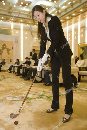 A Woman From the Chinese State Sports Commission Demonstrates Reproduction 'Chuiwan' Or 'Strike Ball' Kit at a Press Conference in Beijing's Great Hall of the People by State Sports Officials Who Claim It is the Original Form of Golf Wednesday 26 April 2006 the Claim is Based Upon a Series of Books and Paintings Dating Back to the Yuan Dynasty (13th Century Ad) Which Show Members of the Imperial Court Enjoying an 'Elegant Sport' Involving Clubs of Carved Precious Woods and Balls of Wood and Jade That Were Struck Into Holes Much Like Modern Golf Whether the Scottish Form of the Game Has Any Relation to This Find Beyond Coincidence Remains to Be Proved