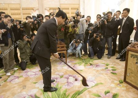 An Official From the Chinese State Sports Commission Demonstrates Reproduction 'Chuiwan' Or 'Strike Ball' Kit at a Press Conference in Beijing's Great Hall of the People by State Sports Officials Who Claim It is the Original Form of Golf Wednesday 26 April 2006 the Claim is Based Upon a Series of Books and Paintings Dating Back to the Yuan Dynasty (13th Century Ad) Which Show Members of the Imperial Court Enjoying an 'Elegant Sport' Involving Clubs of Carved Precious Woods and Balls of Wood and Jade That Were Struck Into Holes Much Like Modern Golf Whether the Scottish Form of the Game Has Any Relation to This Find Beyond Coincidence Remains to Be Proved
