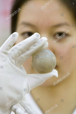 An Assistant Demonstrates a Reproduction 'Chuiwan' Or 'Strike Ball' Jade Ball at a Press Conference by Chinese State Sports Officials in Beijing's Great Hall of the People Who Claim It is the Original Form of Golf Wednesday 26 April 2006 the Claim is Based Upon a Series of Books and Paintings Dating Back to the Yuan Dynasty (13th Century Ad) Which Show Members of the Imperial Court Enjoying an 'Elegant Sport' Involving Clubs of Carved Precious Woods and Balls of Wood and Jade That Were Struck Into Holes Much Like Modern Golf Whether the Scottish Form of the Game Has Any Relation to This Find Beyond Coincidence Remains to Be Proved