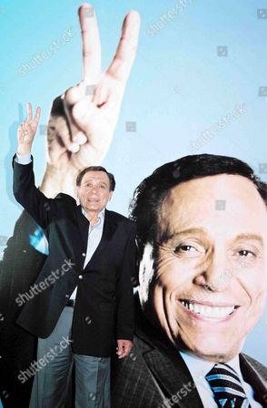 Stock Photo of Famous Egyptian Artist Adel Emam Flashes the Victory Sign in Front of a Poster of Him During Celebrations of the Beginning of the Shooting of the New Film 'Alsafara Fe Alemara' in Cairo Sunday 08 May 2005