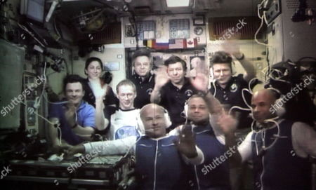 The Screen in the Russian Mission Control Centre Shows Newest Iss Crew Members U S Astronaut Jeffrey Williams (front Row L) Russian Cosmonaut Maxim Surayev (front Row C) Canadian Billionaire and Founder of Cirque Du Soleil Spaceflight Participant Guy Laliberte (front Row R) and Acting Iss Crew Members (unidentified) Talking to Specialists Relatives and Journalists After Successful Docking of Soyuz Tma-16 at the International Space Station (iss) in the City of Korolyov Outside Moscow Russia 02 October 2009 Soyuz Tma-16 Was Launched From Baikonur Cosmodrome Kazakhstan On September 30